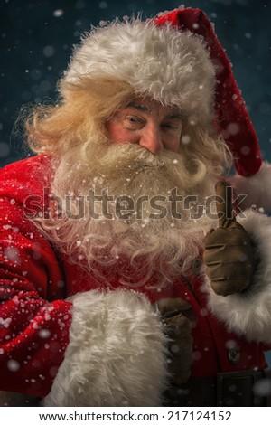 Santa Claus standing under snowfall and thumbs up - stock photo