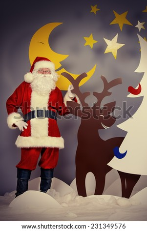 Santa Claus standing with a reindeer in a cartoon fairy snowy forest. Full length portrait.