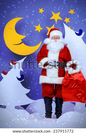 Santa Claus standing with his bag of giftsin a cartoon fairy snowy forest. Full length portrait. - stock photo