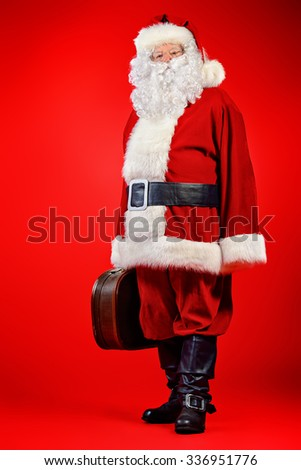 Santa Claus stands with old suitcase over red background. Christmas time. - stock photo