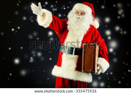 Santa Claus stands with suitcase and shows the direction, black background. Christmas time.  - stock photo