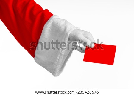 Santa Claus theme: Santa's hand holding a blank red card on a white background - stock photo