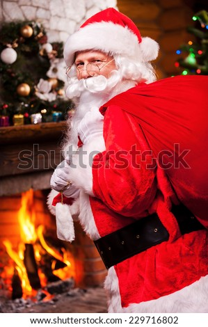 Santa Claus. Traditional Santa Claus carrying sack with presents and smiling with Christmas Tree and fireplace in the background