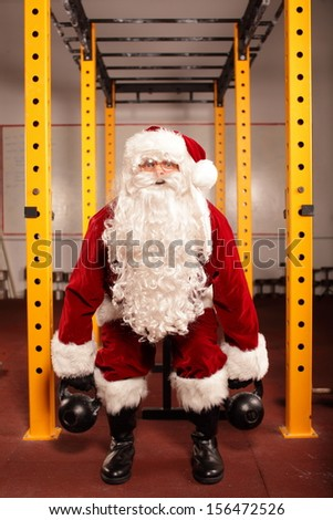 Santa Claus training before Christmas in gym - kettlebells  - stock photo