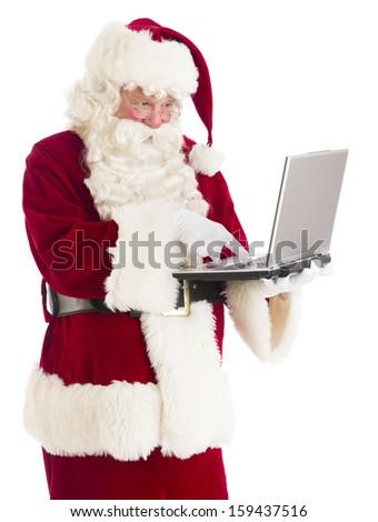 Santa Claus typing on laptop - stock photo