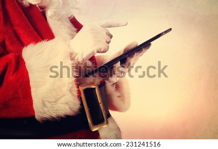 Santa Claus using a digital tablet in vintage style - stock photo
