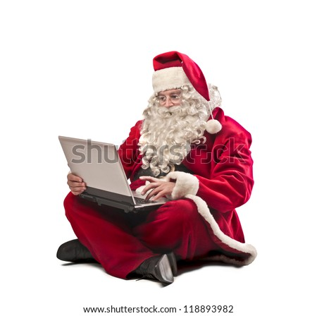 Santa Claus using a laptop computer - stock photo