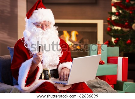 Santa Claus using computer purchasing Christmas presents on internet paying with credit card.? - stock photo
