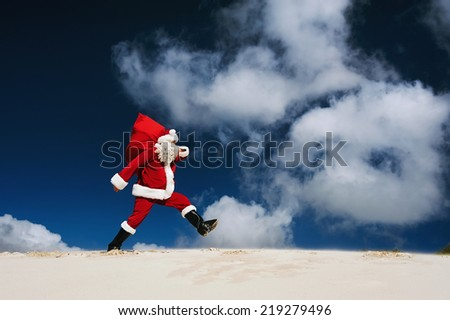Santa Claus walking along the beach holding a sack of presents with copyspace with clouds and sky - stock photo
