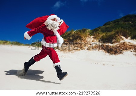 Santa Claus walking along the beach in an out of context situation - stock photo