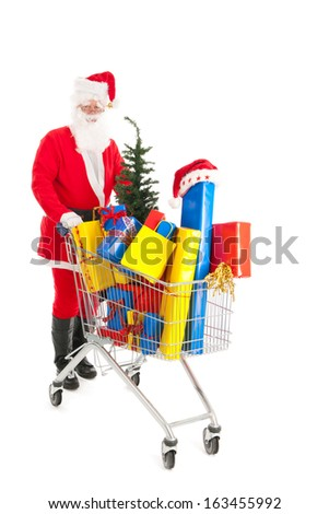 Santa Claus walking with shopping cart full luxury presents and tree - stock photo