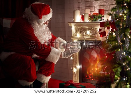 Santa Claus warming his hands at fire fireplace. - stock photo