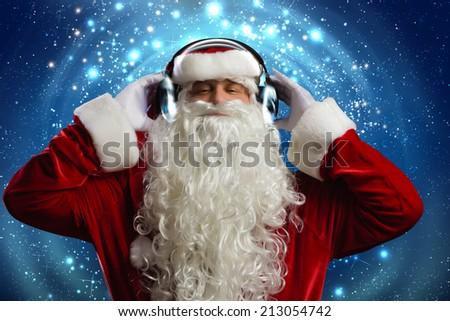 Santa Claus wearing headphones and enjoying music - stock photo