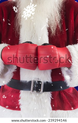 Santa Claus wears boxing gloves against blue snowflake background - stock photo