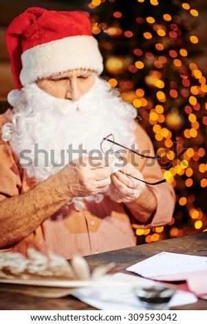 Santa Claus wiping his eyeglasses - stock photo