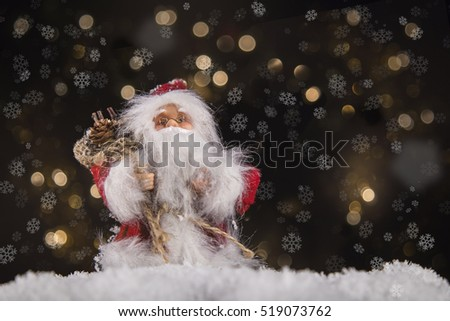 Santa Claus with a bag full of presents in front of abstract christmas background.