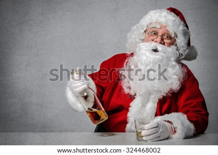 Santa Claus with a bottle of whisky enjoying a drink and taking a rest - stock photo