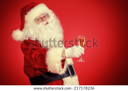 Santa Claus with a glass of champagne wishes all a Merry Christmas. Over festive red background. - stock photo