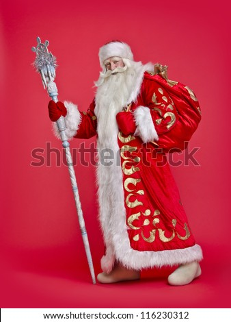 Santa Claus with a sack on a red background - stock photo