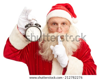 Santa Claus with alarm clock showing five minutes to midnight making shhh gesture and looking at camera - stock photo