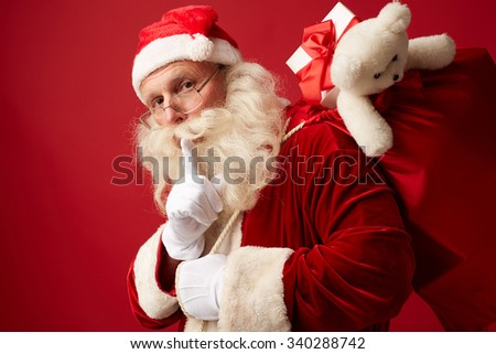 Santa Claus with big red sack keeping his forefinger by mouth
