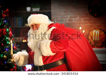 Santa Claus with candle Christmas interior background