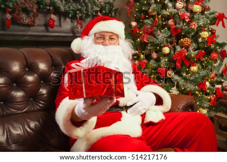 Santa Claus with giftbox on background of sparkling firtree. Christmas