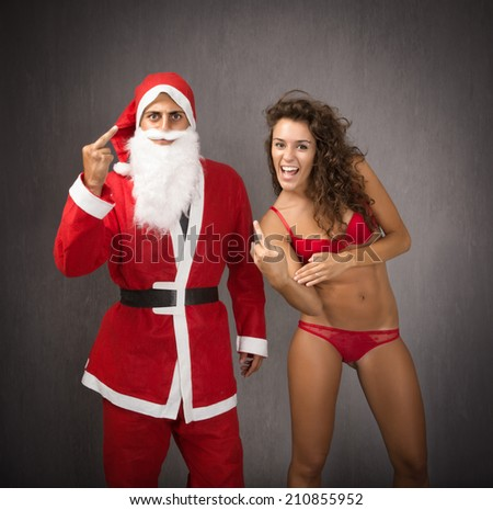 Santa Claus with girl showing rude gesture - stock photo