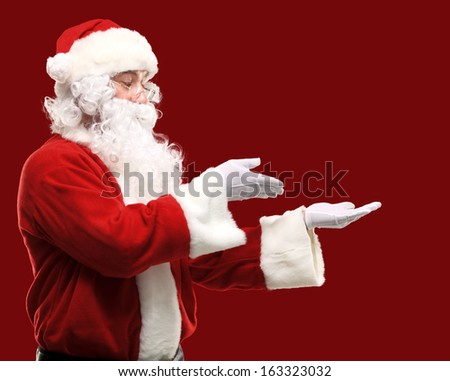 Santa Claus with his arms out in a presenting gesture. Isolated design element