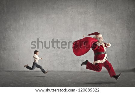 Santa Claus with his bag full of gifts runs away from a child who chases - stock photo