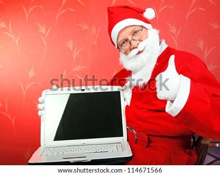 santa claus with laptop computer with empty screen on the red wall background - stock photo