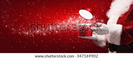 Santa Claus with magic box and snow on red background - stock photo