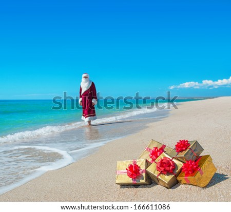 Santa Claus with many golden gifts relaxing on sandy sea beach - christmas or happy new year concept - stock photo
