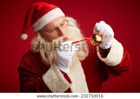 Santa Claus with paintbrush painting snowflakes on red toy ball - stock photo