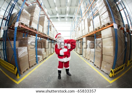 Santa Claus with red sack in storehouse full of presents - fish-eye lens - stock photo