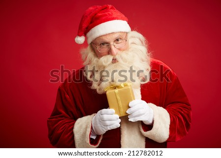 Santa Claus with small golden giftbox looking at camera - stock photo
