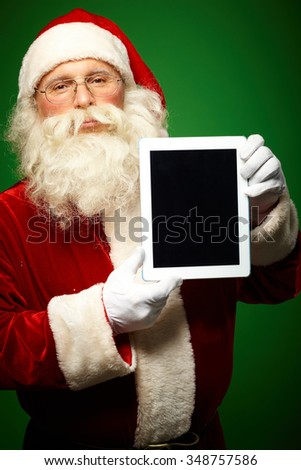 Santa Claus with touchpad looking at camera - stock photo