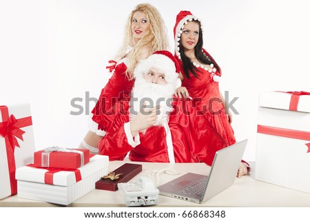 Santa Claus with two sexy helpers, one blonde girl and one brunette girl, being busy before Christmas and getting gifts ready. See more in my portfolio - stock photo