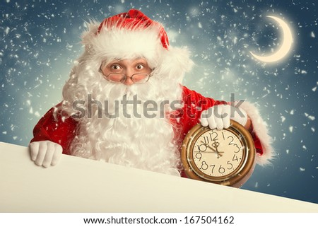 Santa Claus  with white blank banner holding a clock showing several  minutes to midnight - stock photo