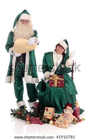 Santa Claus with Xmas woman in green costume surrounded with presents, gifts  and holly branches.  studio shot, white background