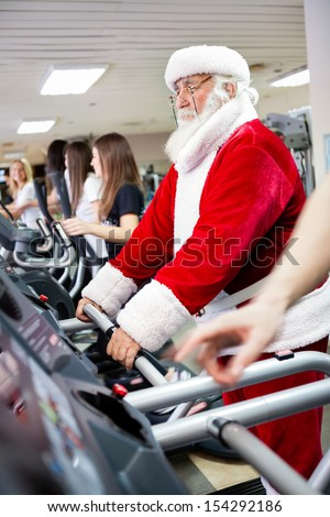 Santa Claus workout  on a treadmill at gym - stock photo
