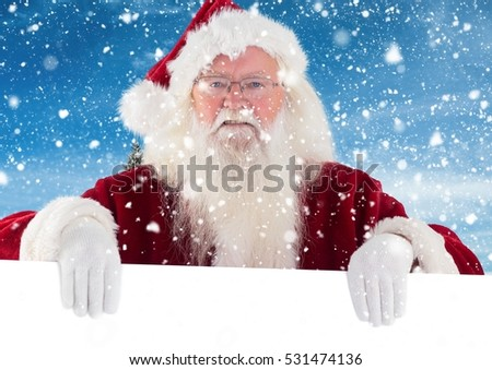 Santa clause holding white placard during snowfall