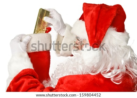 Santa Clause putting a shiny Christmas present into a stocking.  Isolated on white.   - stock photo
