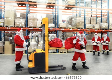 santa clauses in the line for the sacks of gifts in storehouse - stock photo