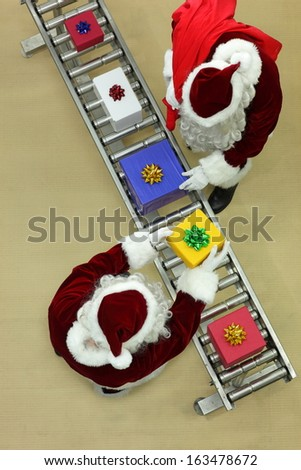 santa clauses working at conveyor belt in Christmas factory - stock photo