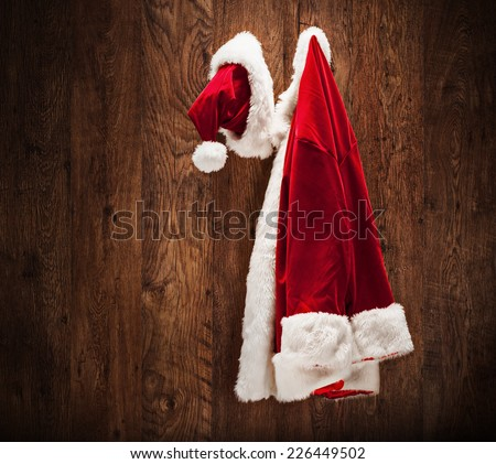 Santa costume hanging on a wooden wall shot with a tilt and a shift lens - stock photo