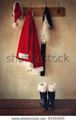 Santa costume with boots on  coat hook - stock photo