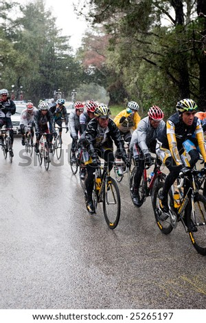 SANTA CRUZ, CA - February 16, 2009: Bicyclers in the Amgen Tour of California 2009 race riding through a rainstorm in the Santa Cruz Mountains on February 16, 2009. - stock photo