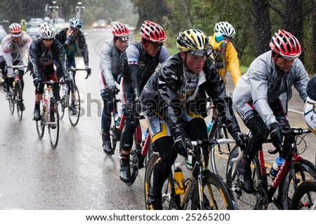 SANTA CRUZ, CA - February 16, 2009: Bicyclers in the Tour of California 2009 race riding through a rainstorm in the Santa Cruz Mountains on February 16, 2009. - stock photo