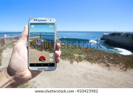 "SANTA CRUZ, CALIFORNIA - JULY 10, 2016: The hit augmented reality smartphone app ""Pokemon GO"" shows a Pokemon encounter overlain on the real world on July 10, 2016 in Santa Cruz, California. - stock photo"